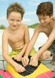 Two boys untangling kite string on beach
