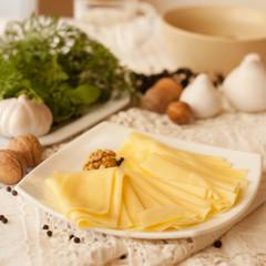 ser żółty na biały talerz z orzechy i pieprz