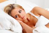 Frau liegt wach im Bett.