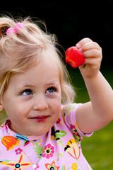 Kind beim Essen einer Erdbeere im Garten