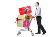 Man pushing a shopping cart full with presents
