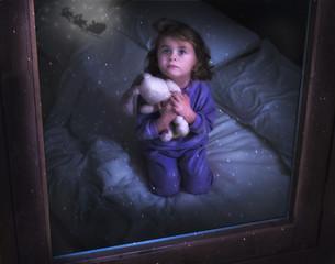 Bambina con orsacchiotto che guarda Babbo Natale dalla finestra