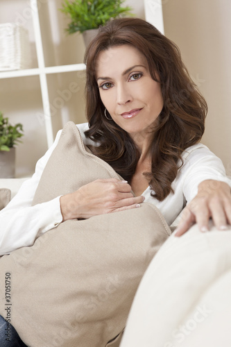 Brunette Woman Sitting Thinking At Home on Sofa
