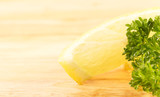 lemon wedge and parsley on a cutting board
