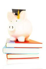 piggy bank on book pile - student debt concept