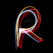Letter R made from brightly coloured neon lights