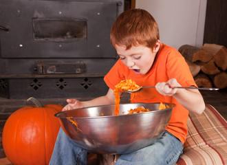 young boy eating pumpkins