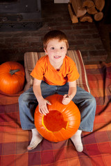 young boy carving pumkins