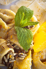 Close-up on tortellini with fennel, orange and mint.