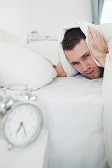 Portrait of a man covering his ears with a duvet while his alarm