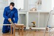 Young handyman cutting a wooden board