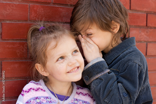 two kids sharing a secret