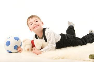 Мальчик с игрушками лежит на полу