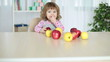 Baby girl eats apples sitting at the table