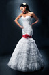 Bride in a white dress decorated with red sash