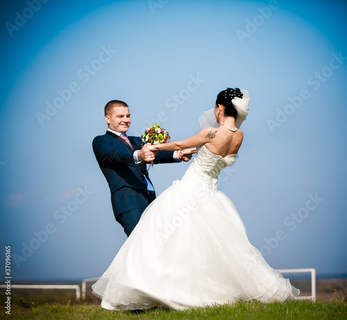 Newly married couple dancing in field