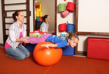 Kind bei der Physiotherapie mit Medizinball
