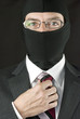 Businessman In Balaclava Adjusts Tie, One Hand