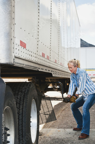 Woman Truck Driver Raising Trailer legs