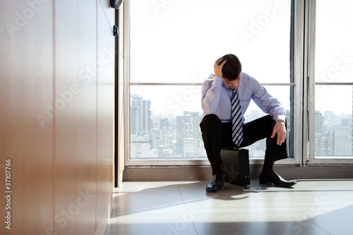 Upset Business man Sitting on Briefcase