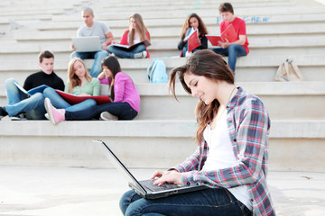 students working with laptops and books on campus