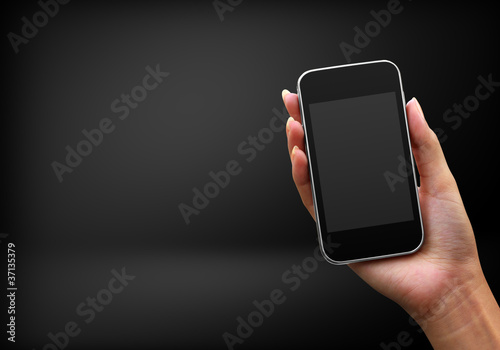 Mobile phone in woman hand on black background