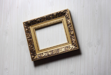 Image of lopsided golden art frame on the wall in dramatic light