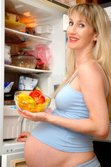 The pregnant woman with salad in hands