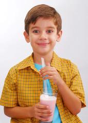 Niño bebiendo batido de fresas.