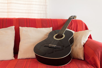 Guitar on a red sofa