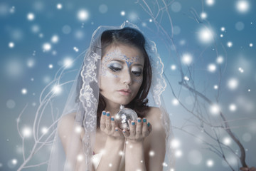Beautiful woman with disco ball and snow