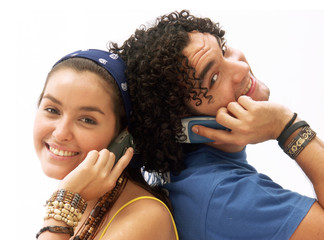 Pareja joven conversando por teléfono celular.