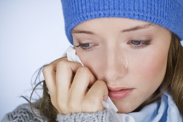 A woman crying, wiping her tears away with a tissue