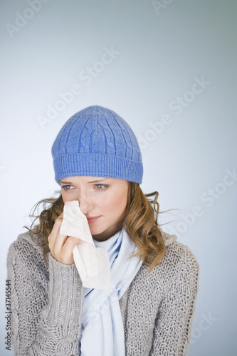 A young woman wiping her tears away with a tissue
