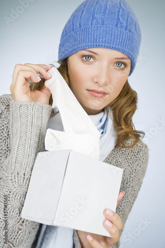A young woman taking a tissue out of a tissue box