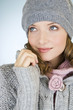 A young woman wearing a grey woollen hat, looking up