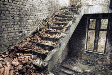 Collapsed roof tiles on a staircase in a derelict building