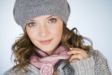 Portrait of a young woman wearing a grey woollen hat, smiling