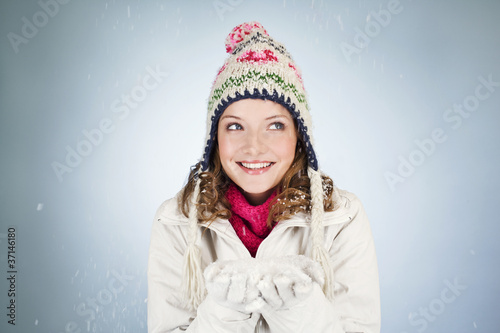 A young woman holding a handful of snow, smiling