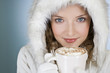 A woman wearing a winter coat, holding a mug of hot chocolate