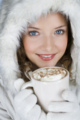 A woman wearing a winter coat, holding a mug of hot chocolate