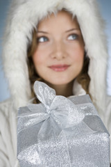 A young woman wearing a winter coat, holding a Christmas present