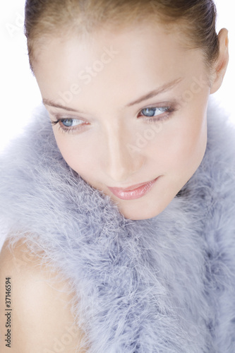 Portrait of a young woman wearing a feather shrug, looking away