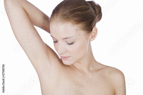 A young woman looking at her armpit