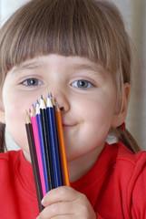 Niña sujetando unos lápices de colores.