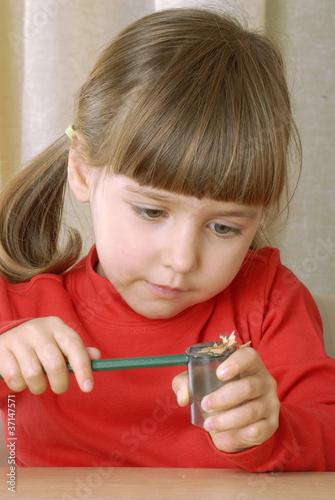 Niña sacando punta a un lápiz.