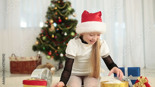 Happy girl in santa cap gets a teddy bear out of the gift box