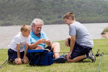 grandpa teaching grandsons how to put bait on fishing hook
