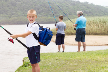 happy little boy fishing with family by the lake