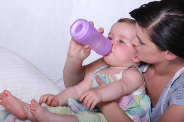 Young mother giving her baby a drinks bottle